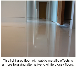 A floor with light grey colour and subtle metallic effects, which is an example of a good alternative to white glossy floors.