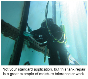 A diver applying a moisture-tolerant coating underwater in a tank repair application.