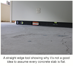 A straight edge tool showing that a concrete slab isn't flat.