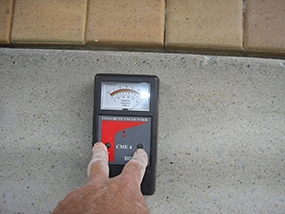 A contractor conducting substrate assessment with a moisture meter.
