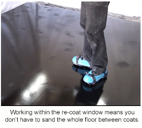 A black epoxy floor with dull patches from being sanded with a pole sander.