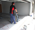 Applicator grinding garage floor.
